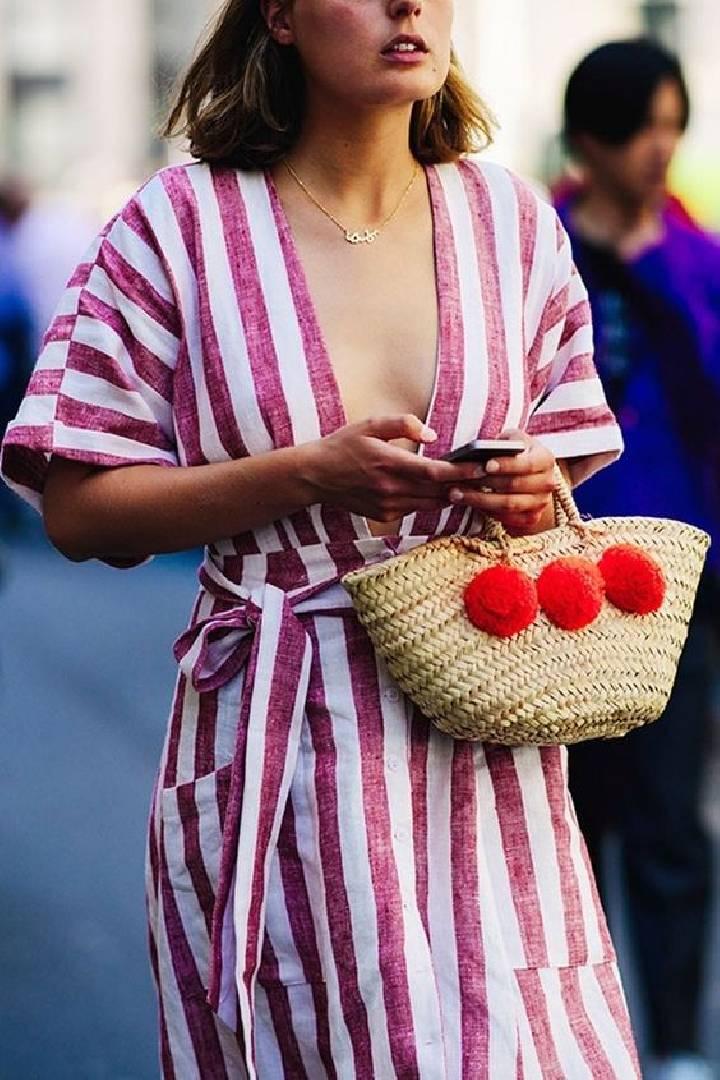 un sac en forme de panier avec de grands pompons rouges