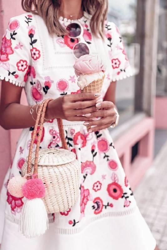 un sac en paille blanc avec une poignée en cuir, des pompons et une forme unique