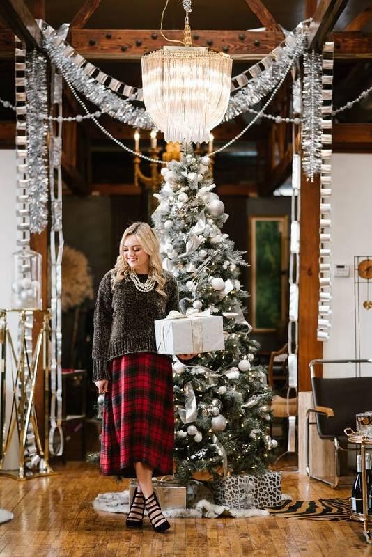 un look simple et élégant avec un sweat-shirt gris surdimensionné une jupe midi asymétrique à carreaux, des colliers superposés et des chaussures à lanières