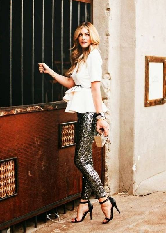 une chemise blanche au peplum, un pantalon noir à paillettes, des talons noirs et une pochette métallique