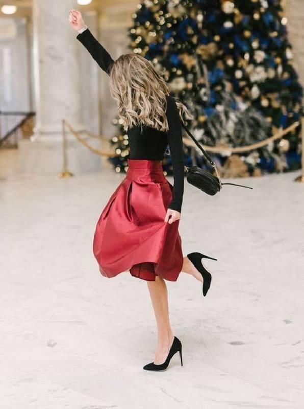 un col roulé noir, une jupe rouge foncé en ligne A, des talons noirs et un sac pour une tenue de Noël élégante qui ne nécessite pas d'achats