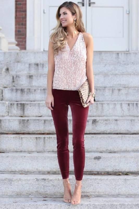 un look de vacances avec un haut à paillettes roses, un pantalon en velours bordeaux, des chaussures nues et une pochette à motifs d'animaux