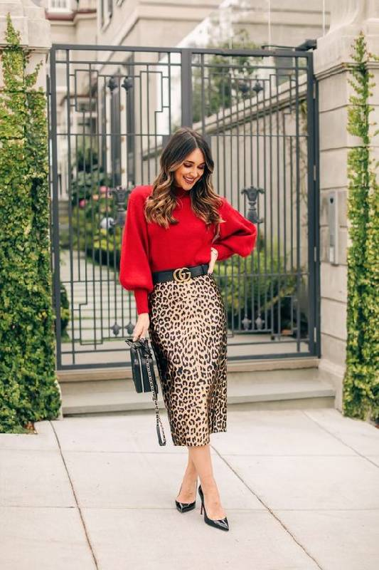un pull rouge, une jupe midi au crayon imprimé léopard, des chaussures noires et un sac noir pour une sensation de raffinement