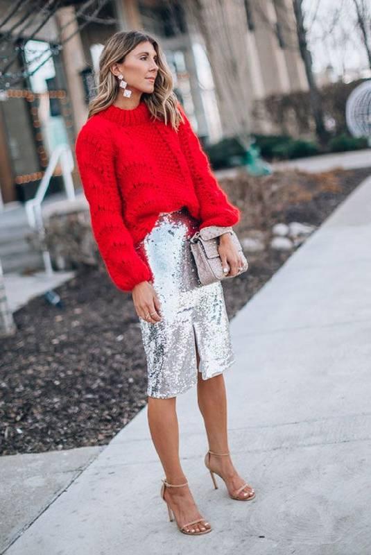 un chandail rouge en tricot, une jupe à paillettes argentées, des chaussures nues et un sac argenté pour les vacances